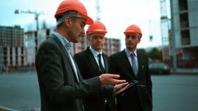 Εργάτης οικοδομών και επιχειρηματίες που μιλούν στην περιοχή απόθεμα βίντεο