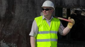 Εργάτης οικοδομών με τη βαρειά κοντά στον τοίχο απόθεμα βίντεο