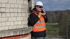 Εργάτης οικοδομών με τη βαρειά που μιλά στο PC ταμπλετών φιλμ μικρού μήκους