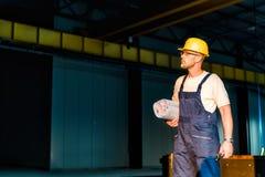 Εργάτης οικοδομών με τις μπλε τυπωμένες ύλες Στοκ Φωτογραφίες