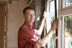 Εργάτης οικοδομών που εγκαθιστά τα νέα παράθυρα στο εσωτερικό Στοκ εικόνα με δικαίωμα ελεύθερης χρήσης