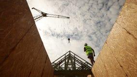 Εργάτης οικοδομών, που εξετάζει επάνω τις ακτίνες στεγών απόθεμα βίντεο