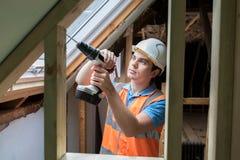Εργάτης οικοδομών που χρησιμοποιεί το τρυπάνι για να εγκαταστήσει το παράθυρο αντικατάστασης Στοκ Εικόνες
