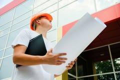 Εργάτης οικοδομών σε μια άσπρη μπλούζα και ένα πορτοκαλί κράνος Στοκ εικόνες με δικαίωμα ελεύθερης χρήσης