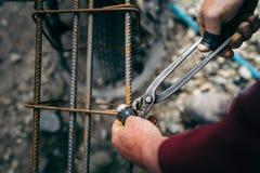 Εργάτης οικοδομών - χέρια που εξασφαλίζουν τους φραγμούς χάλυβα με τη ράβδο καλωδίων για την ενίσχυση του σκυροδέματος Στοκ φωτογραφία με δικαίωμα ελεύθερης χρήσης