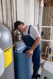 Εργάτης που αντικαθιστά ένα παλαιό εσωτερικό αποσκληρυντικό νερού Στοκ Εικόνα