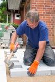 Εργάτης που βάζει τις νέες πέτρες επίστρωσης για ένα patio Στοκ Εικόνες