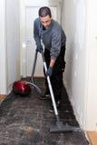 Εργάτης που σκουπίζει μια μετάβαση με ηλεκτρική σκούπα κατά τη διάρκεια των ανακαινίσεων Στοκ Εικόνα