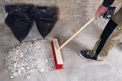 Εργάτης που σκουπίζει τα ερείπια με τη σκούπα Στοκ Φωτογραφία