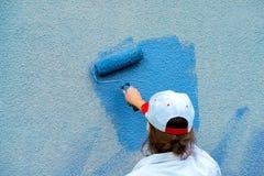 Εργάτης που χρωματίζει τον τοίχο στο μπλε Στοκ Εικόνες