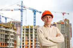 Εργάτης στο κόκκινο κράνος στο υπόβαθρο των κτηρίων Στοκ εικόνα με δικαίωμα ελεύθερης χρήσης