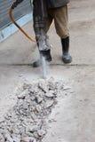 Εργαζομένων συγκεκριμένος δρόμος τσιμέντου ατόμων τρυπώντας με τρυπάνι στοκ εικόνα