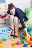 Εργαζόμενη κυρία που καθαρίζει επάνω τα παιχνίδια Στοκ Φωτογραφίες