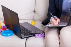 Εργαζόμενη μητέρα μεταξύ των παιχνιδιών Στοκ εικόνα με δικαίωμα ελεύθερης χρήσης
