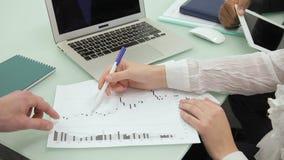 Εργαζόμενη ομάδα που εξετάζει τα έγγραφα, που κάθονται στην κορυφαία επιχείρηση απόθεμα βίντεο