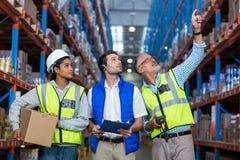Εργαζόμενοι αποθηκών εμπορευμάτων που αλληλεπιδρούν ο ένας με τον άλλον στοκ εικόνες με δικαίωμα ελεύθερης χρήσης