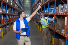 Εργαζόμενοι αποθηκών εμπορευμάτων που αλληλεπιδρούν ο ένας με τον άλλον στοκ εικόνες