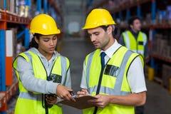 Εργαζόμενοι αποθηκών εμπορευμάτων που αλληλεπιδρούν ο ένας με τον άλλον στοκ φωτογραφίες με δικαίωμα ελεύθερης χρήσης