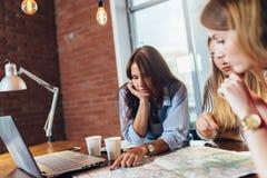 Εργαζόμενοι γραφείων θηλυκών που προγραμματίζουν τις διακοπές που χρησιμοποιούν το χάρτη στοκ εικόνες