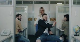 Εργαζόμενοι γραφείων που έχουν τη διασκέδαση στο χρόνο σπασιμάτων, την όμορφη ξανθή επιχειρησιακή γυναίκα και το συνάδελφό της πο απόθεμα βίντεο
