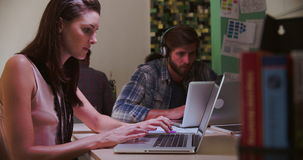 Εργαζόμενοι γραφείων στα γραφεία που λειτουργούν αργά στα lap-top απόθεμα βίντεο
