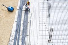 Εργαζόμενοι εργοτάξιων οικοδομής στο κτήριο βάσεων ράβδων χάλυβα πατωμάτων τσιμέντου Στοκ Εικόνες