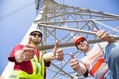 εργαζόμενοι ηλεκτροφόρων καλωδίων με τους αντίχειρες επάνω στοκ φωτογραφία με δικαίωμα ελεύθερης χρήσης