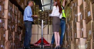 Εργαζόμενοι και διευθυντής αποθηκών εμπορευμάτων που μιλούν από την παλέτα απόθεμα βίντεο
