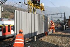 Εργαζόμενοι κατά τη διάρκεια της εγκατάστασης των εμποδίων θορύβου στο σιδηρόδρομο Στοκ εικόνα με δικαίωμα ελεύθερης χρήσης