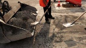 Εργαζόμενοι με τα φτυάρια που ρίχνουν την άσφαλτο φιλμ μικρού μήκους