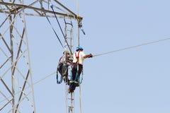 Εργαζόμενοι πέρα από έναν πύργο υψηλής έντασης που κάνει τις επιδιορθώσεις στοκ εικόνα