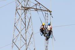 Εργαζόμενοι πέρα από έναν πύργο υψηλής έντασης που κάνει τις επιδιορθώσεις στοκ εικόνες