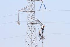 Εργαζόμενοι πέρα από έναν πύργο υψηλής έντασης που κάνει τις επιδιορθώσεις στοκ εικόνες με δικαίωμα ελεύθερης χρήσης