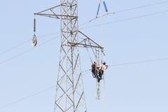 Εργαζόμενοι πέρα από έναν πύργο υψηλής έντασης που κάνει τις επιδιορθώσεις στοκ φωτογραφία