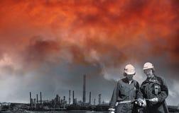 Εργαζόμενοι πετρελαίου μπροστά από τις γιγαντιαίες εγκαταστάσεις καθαρισμού Στοκ εικόνα με δικαίωμα ελεύθερης χρήσης