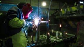 Εργαζόμενοι που αλέθουν και που ενώνουν στενά την καρέκλα μετάλλων στο εργοστάσιο απόθεμα βίντεο