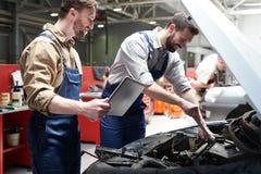 Εργαζόμενοι που ελέγχουν το αυτοκίνητο στην υπηρεσία στοκ φωτογραφία