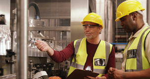 Εργαζόμενοι που ελέγχουν τα μπουκάλια στη γραμμή παραγωγής