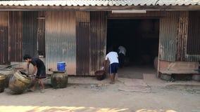 Εργαζόμενοι που κυλούν τα μεγάλα βάζα νερού δράκων από το κάψιμο του φούρνου φιλμ μικρού μήκους
