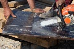 Εργαζόμενοι που κόβουν τη σανίδα με το αλυσιδοπρίονο Στοκ Εικόνες