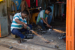 Εργαζόμενοι που κόβουν τις λεπτομέρειες μετάλλων που χρησιμοποιούν το ηλεκτρικό πριόνι Στοκ εικόνες με δικαίωμα ελεύθερης χρήσης