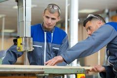 Εργαζόμενοι που φορούν τα καλύμματα αυτιών που χρησιμοποιούν το πριόνι στοκ φωτογραφία