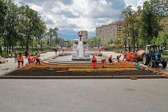 Εργαζόμενοι που φυτεύουν κόκκινα begonias στο κρεβάτι λουλουδιών στην πλατεία Pushkin στη Μόσχα στοκ φωτογραφία
