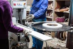 Εργαζόμενοι που χρησιμοποιούν τη μηχανή ακρών για να κάνει τα έπιπλα στις εργασίες ξυλουργών Στοκ Εικόνα