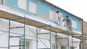 Εργαζόμενοι που χρωματίζουν από τον τοίχο οικοδόμησης πινέλων απόθεμα βίντεο