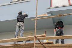 Εργαζόμενοι που χρωματίζουν και που επισκευάζουν την πρόσοψη Στοκ φωτογραφία με δικαίωμα ελεύθερης χρήσης