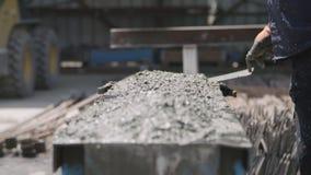 Εργαζόμενοι που χύνουν το σκυρόδεμα στις μεγάλες φόρμες χάλυβα σε ένα εργοτάξιο οικοδομής απόθεμα βίντεο