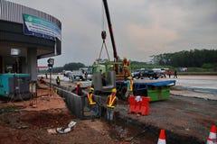 Εργαζόμενοι προγράμματος κατά τη χειρισμό των υδάτινων οδών στην κατασκευή στοκ εικόνα