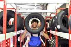 Εργαζόμενοι σε μια αποθήκη εμπορευμάτων με τα ελαστικά αυτοκινήτου για την αλλαγή του αυτοκινήτου Στοκ Εικόνες