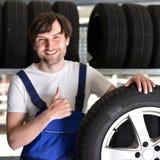 Εργαζόμενοι σε μια αποθήκη εμπορευμάτων με τα ελαστικά αυτοκινήτου για την αλλαγή του αυτοκινήτου Στοκ φωτογραφία με δικαίωμα ελεύθερης χρήσης